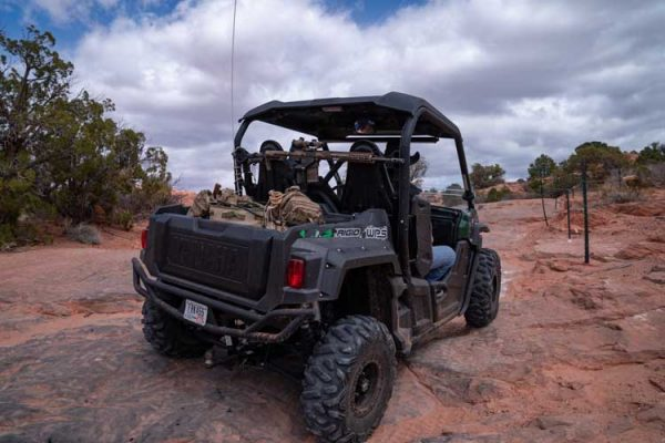 An AR-15 is mounted on a Blac-Rac 1070 with an integral lock. The Blac-Rac is mounted on a tube mount in a Yamaha Wolverine UTV. The UTV travels down an off-road path in the Utah desert.