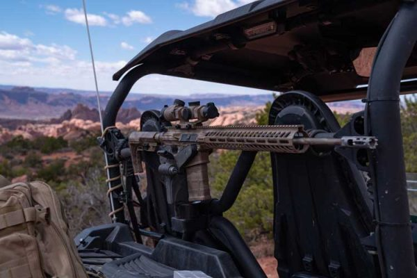 An AR-15 is mounted on a Blac-Rac 1070 with an integral lock on a tube mount in a Yamaha Wolverine UTV in the Utah desert.