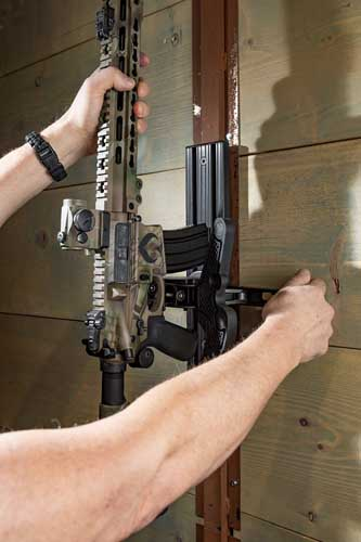 "A firearm owner unlocks an AR 15, releasing it from a Blac-Rac 1070 Weapon Retention System, wall mounted on an 18"" T-channel."