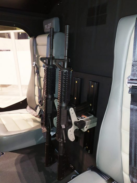 dual 1082 gun racks are mounted between cabin seats in a helicopter